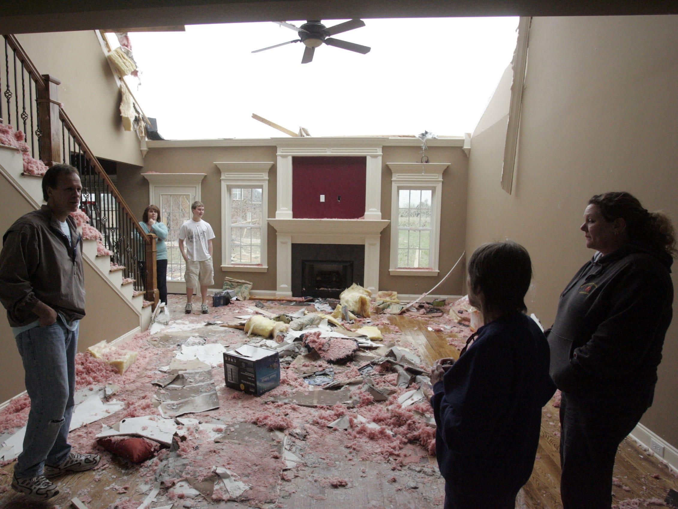 DNJ photo by Aaron Thompson Scott Johnson's, left, Frank Robinson Drive home was damaged by Friday's tornado.