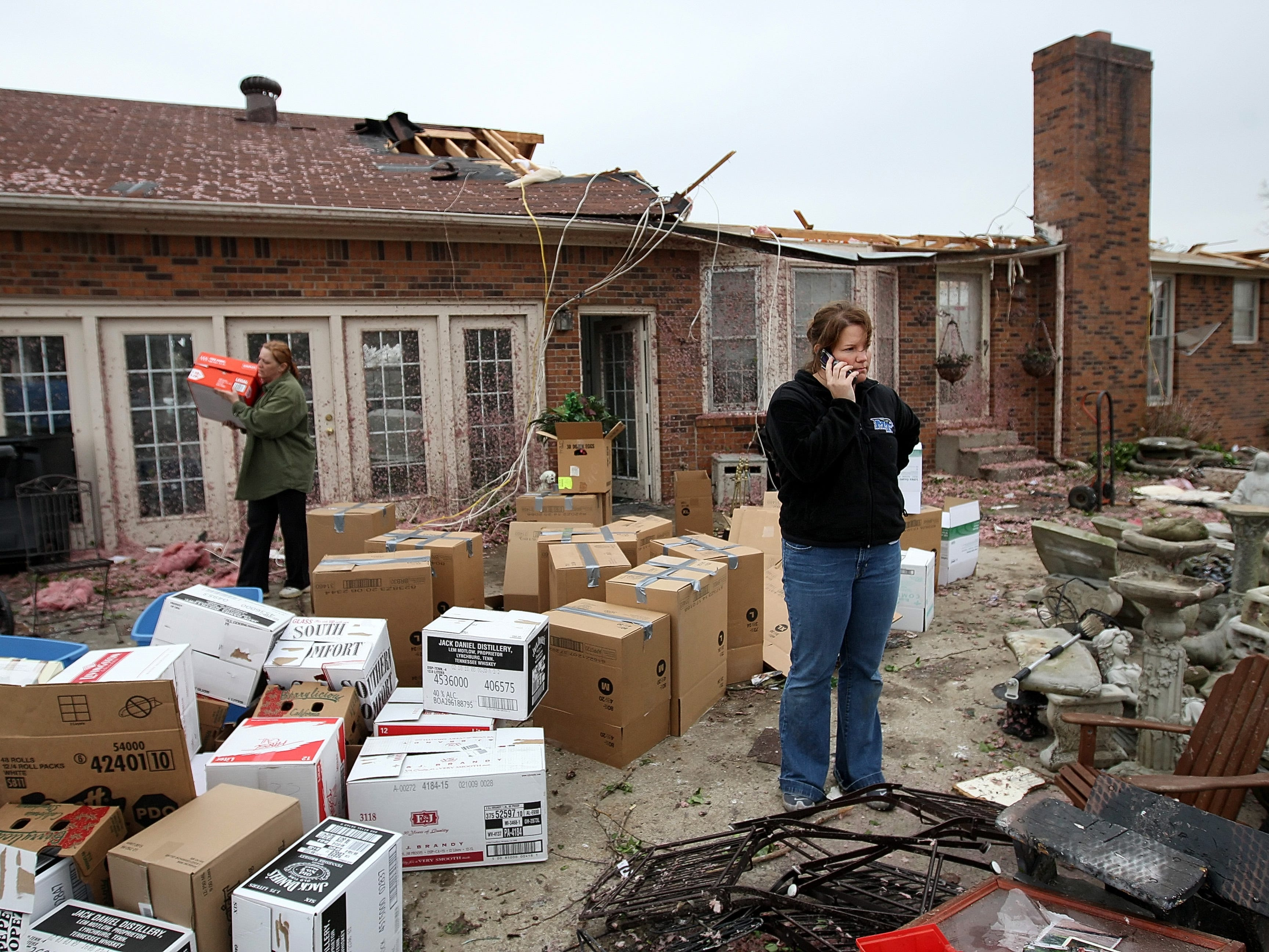 Jaymie Owen, right, talks on the phone while helping to box up her Grandparents belongings after their home was badly damaged in Murfreesboro, Tennessee on Saturday April 11, 2009. (Josh Anderson for The Tennessean)