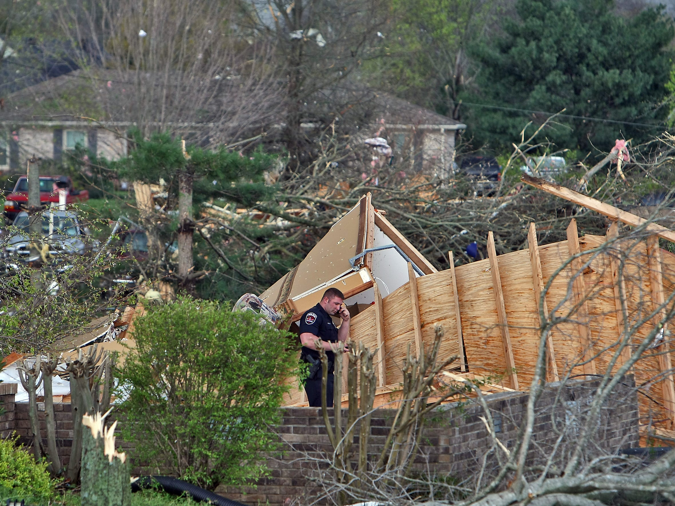 A Murfreesboro police officer surveys the area where tornado swept through on Manson Pike in Murfreesboro, Tenn., Friday, April 10, 2009. (JAE S. LEE / THE TENNESSEAN)