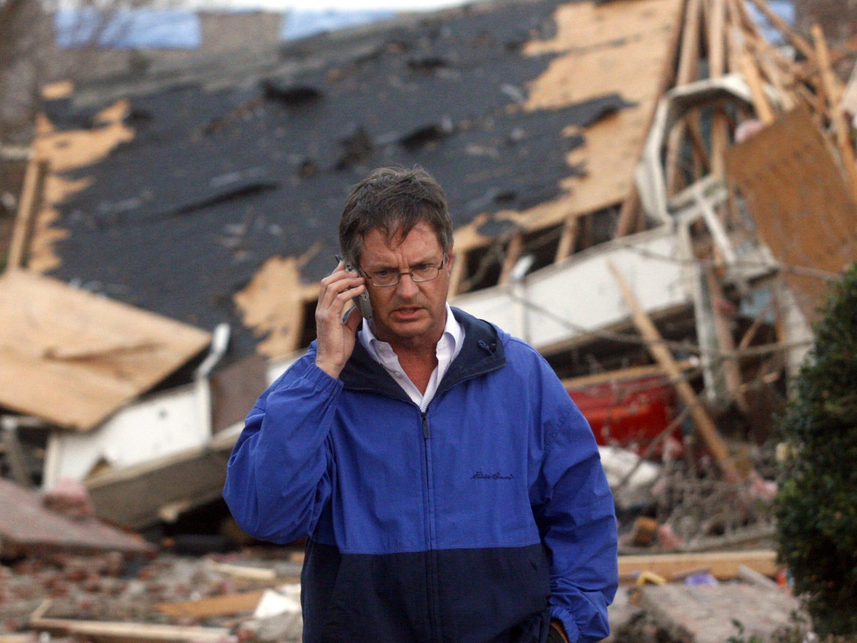 DNJ photo by John A. Gillis    Murfreesboro Mayor Tommy Bragg talks on the phone while inspecting tornado damage on Buckle Street in Murfreesboro Friday, April 10, 2009.