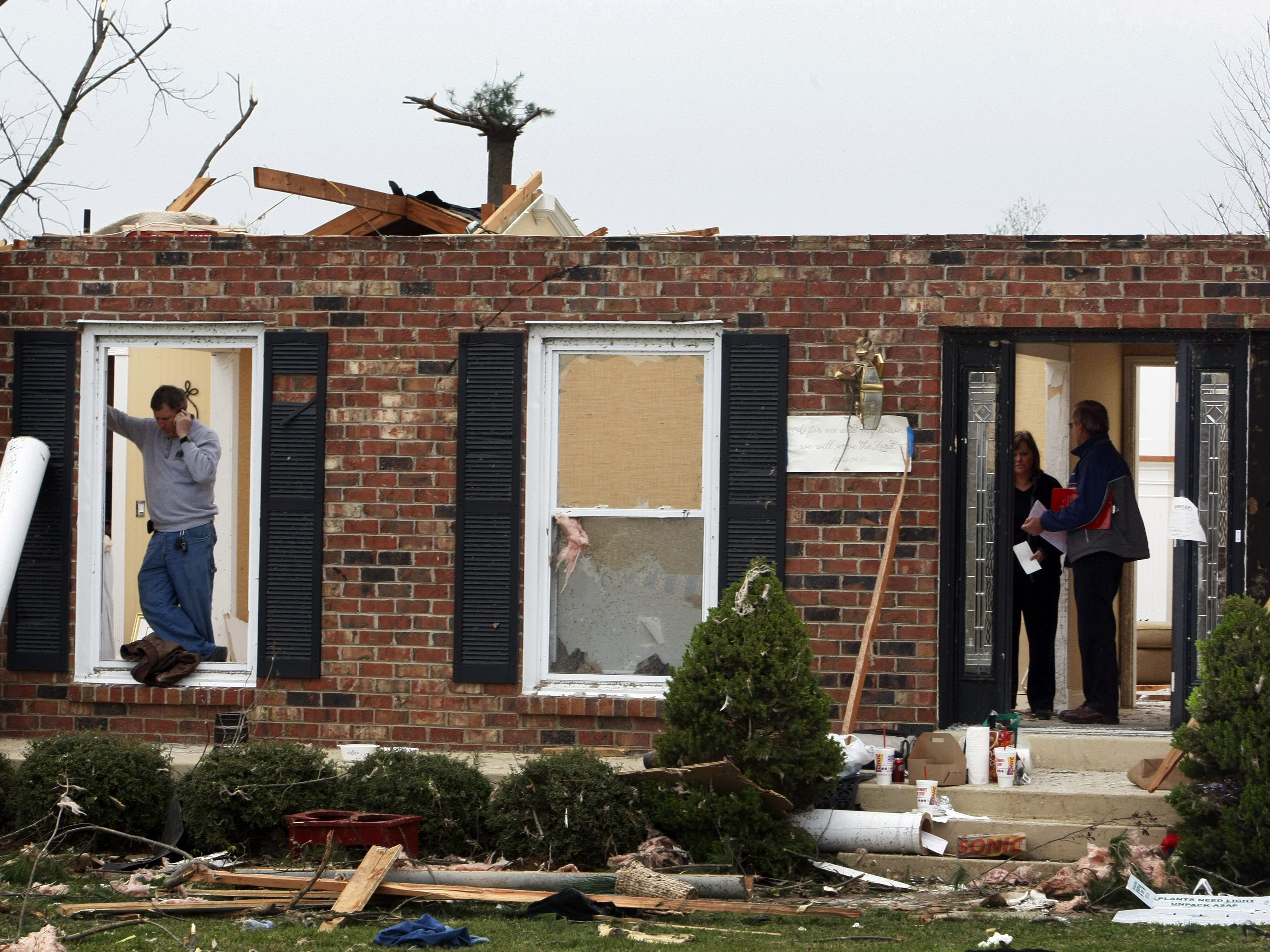 Chris Bloebaum, left, talks on his cell phone as his wife Jenny talks with State Farm Representative J. E. Fields about the loss of their home a day after a tornado roared through Murfreesboro.