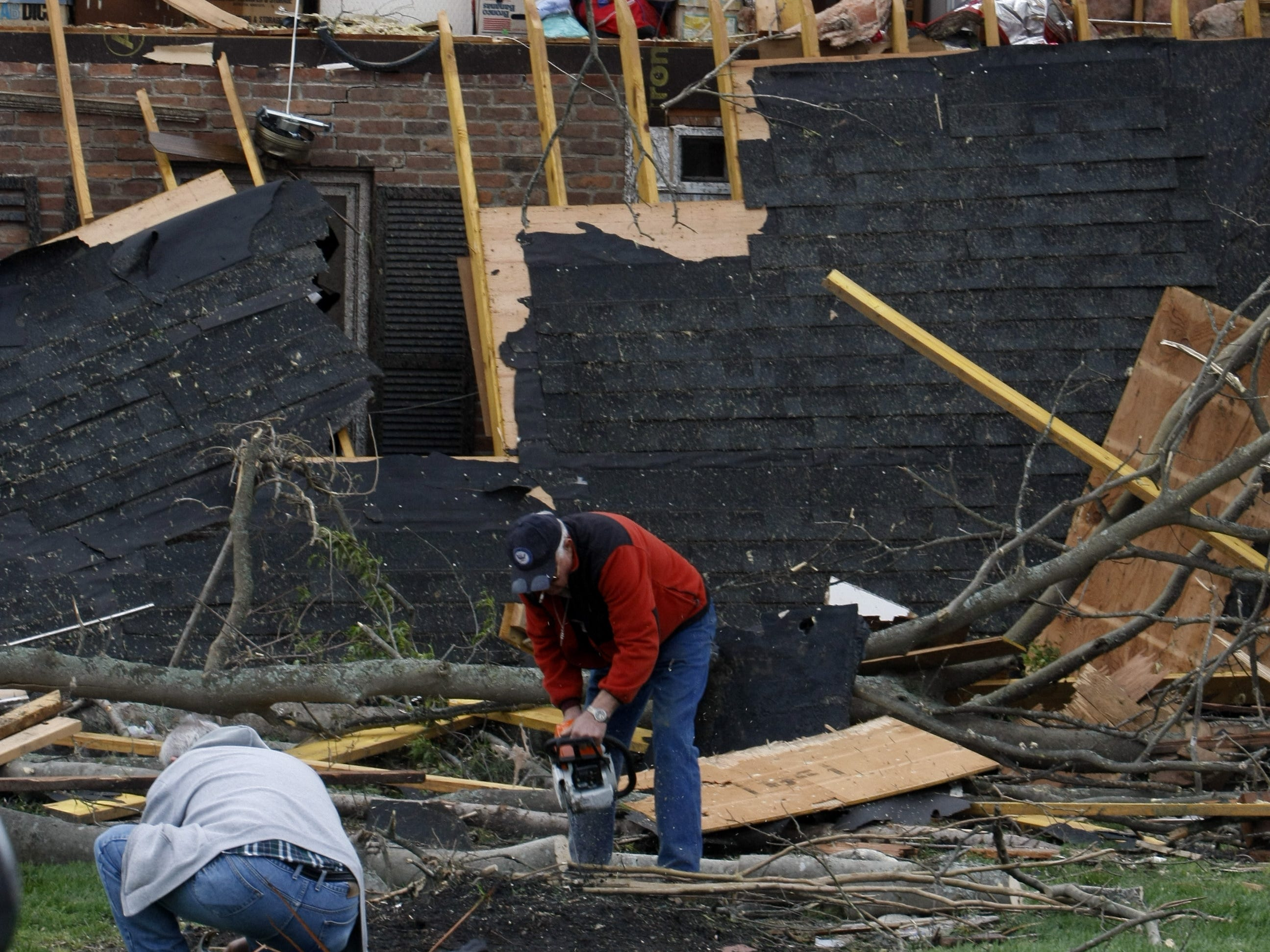 Workers cut limbs and get things cleaned up a day after a tornado roared through Murfreesboro.