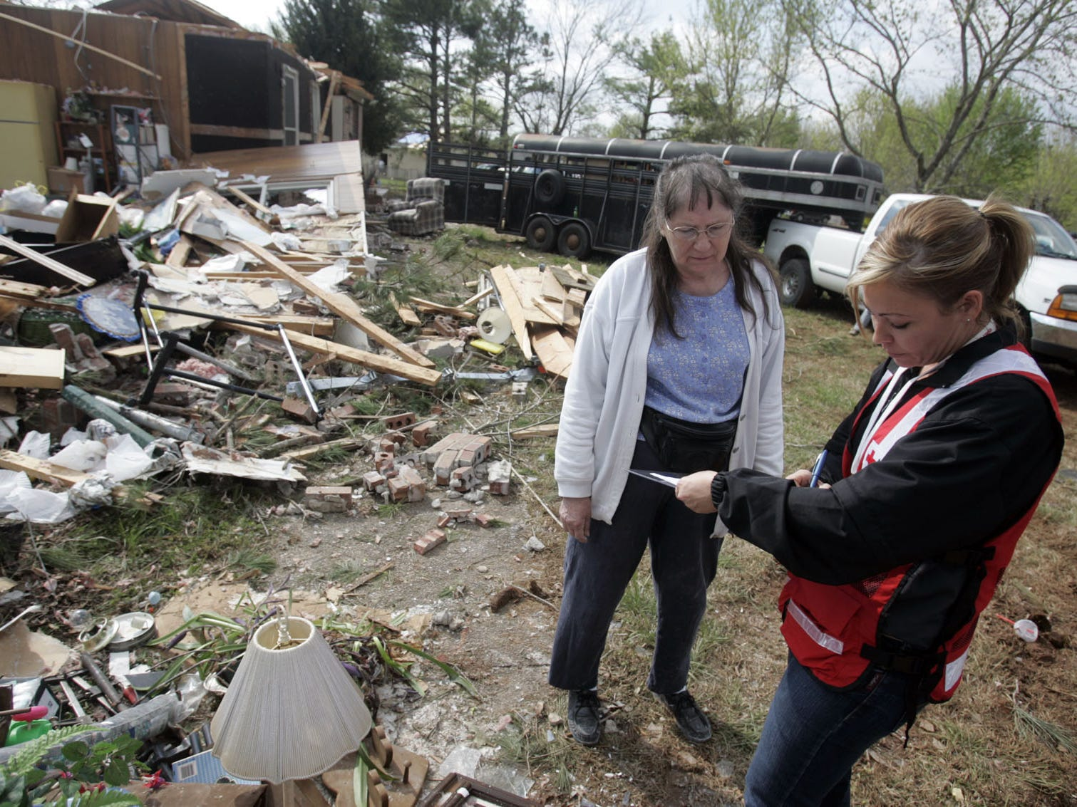 DNJ photo by Aaron Thompson Sabrina Hudgens, right, gathers some information for the American Red Cross Disaster Assement Team from Claudine Johnson abouther damaged home on Esquire Ct. Hudgens has been at volunteer with the Red Cross for 10 years.