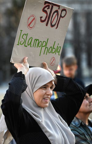 Ammeh Awad hold sign to Stop Islamophobia  during a vigil Sunday to remember 50 people who were killed and more than 34 were wounded in the shootings at two mosques in Christchurch New Zealand Sunday, March 17, 2019, in Nashville, Tenn.