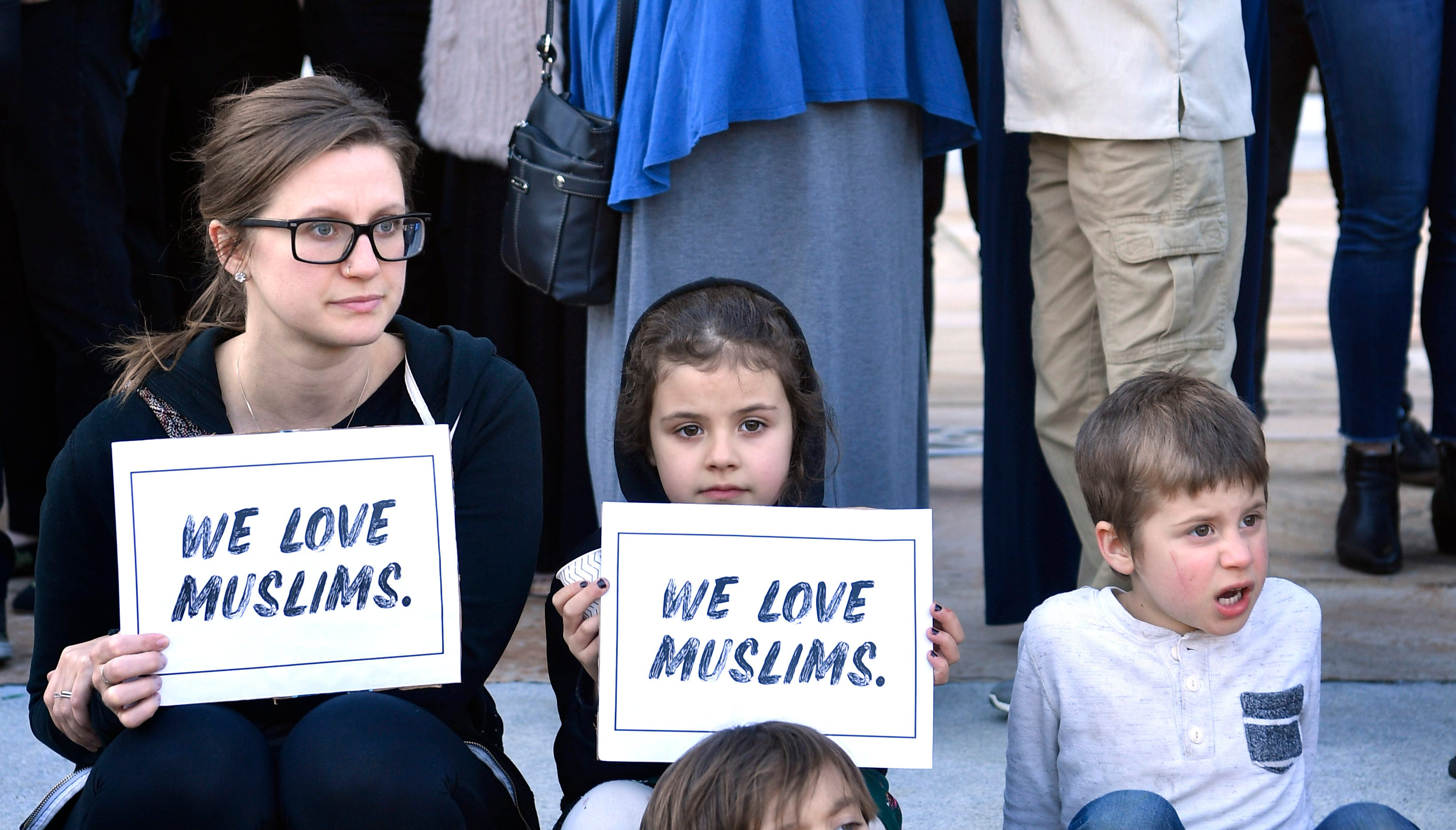 """Becky Laparra wanted to teach her children Solacem Roman and Belle to """"love their neighbors"""" so they came bearing signs to the vigil Sunday to remember 50 people who were killed and more than 34 were wounded in the shootings at two mosques in Christchurch New Zealand Sunday, March 17, 2019, in Nashville, Tenn."""