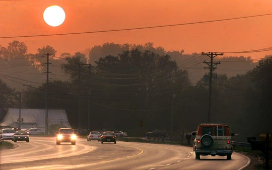 Afternoon commuters along Lebanon Road in Mt. Juliet turn on their car lights as the sun sets earlier with the end of summer and the beginning of fall in 2002.
