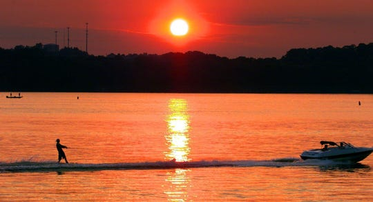 A water skier finds his place in the sun, but not for long as this summer day comes to an end with a brilliant sunset on Old Hickory Lake.