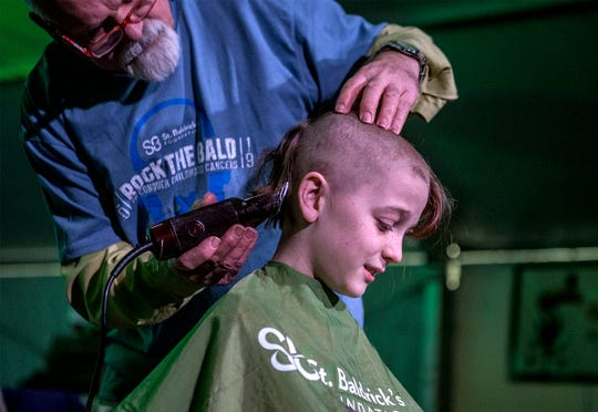 Sam Hannig, 11, has his head shaved by Lanny Austin at the the annual St. Balderick's event to raise money for St. Jude's Children's Hospital. This is the sixth year Hannig has raised money for the event and had his head shaved.