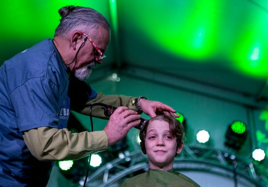 Sam Hannig, 11, has his head shaved by Lanny Austin at the the annual St. Baldericks event to raise money for St. Jude's Children's Hospital. Sam said he intends to return for a seventh round next March.