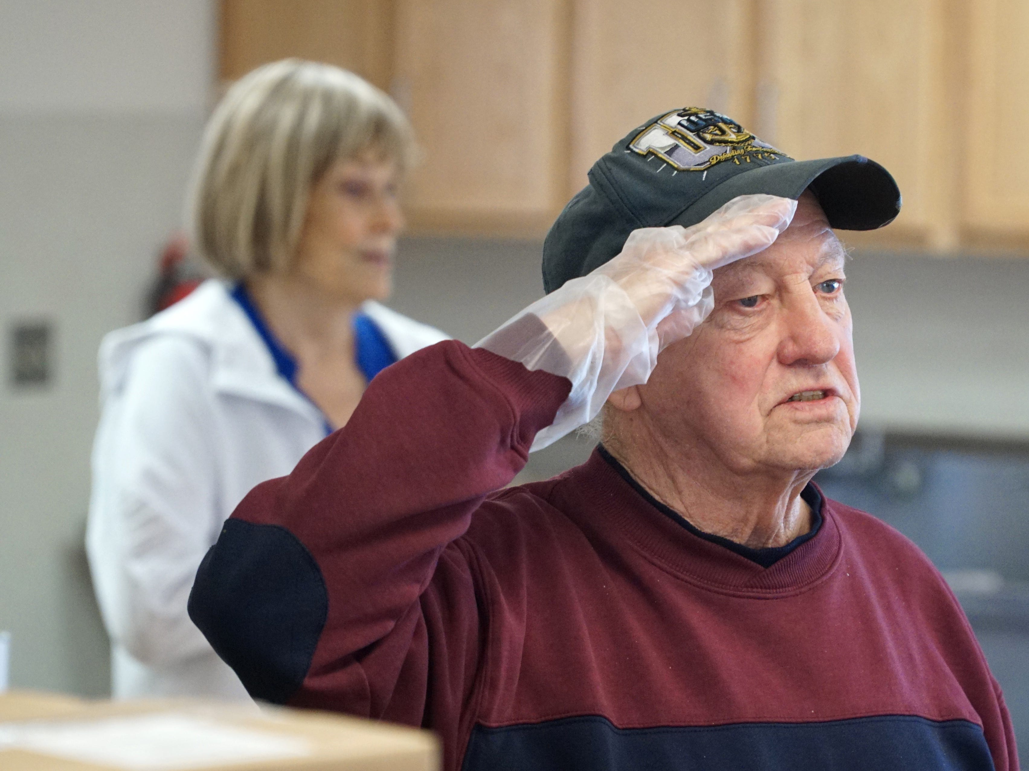 Veteran Roy Brandon salutes the flag.
