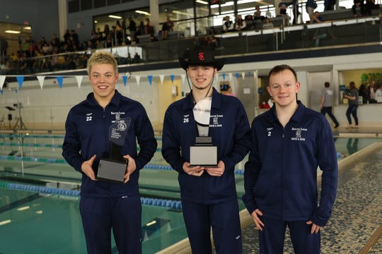 South Lyon Unified swim and dive seniors Christian Entyre, James Perry and Preston Healy pose after winning the 2019 LVC title.
