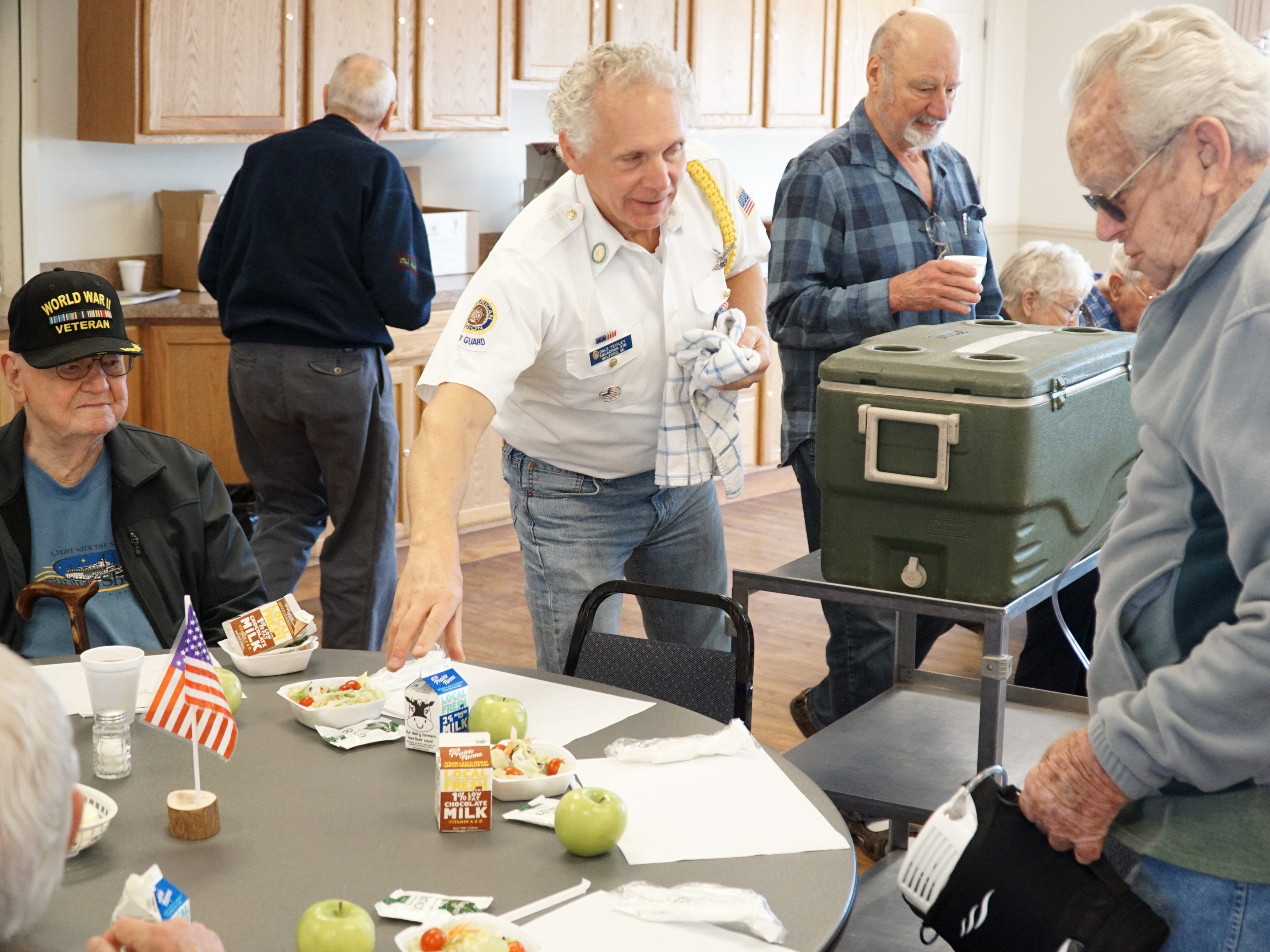 Dale Feigley, center, volunteers at the March 18 Veterans' Lunch at the Miford Senior Center. Feigley, a member of Milford's American Legion Post 216, helps to serve veterans who show up to the center's once-a-month, third Monday in the month lunch where they can socialize and break bread together.
