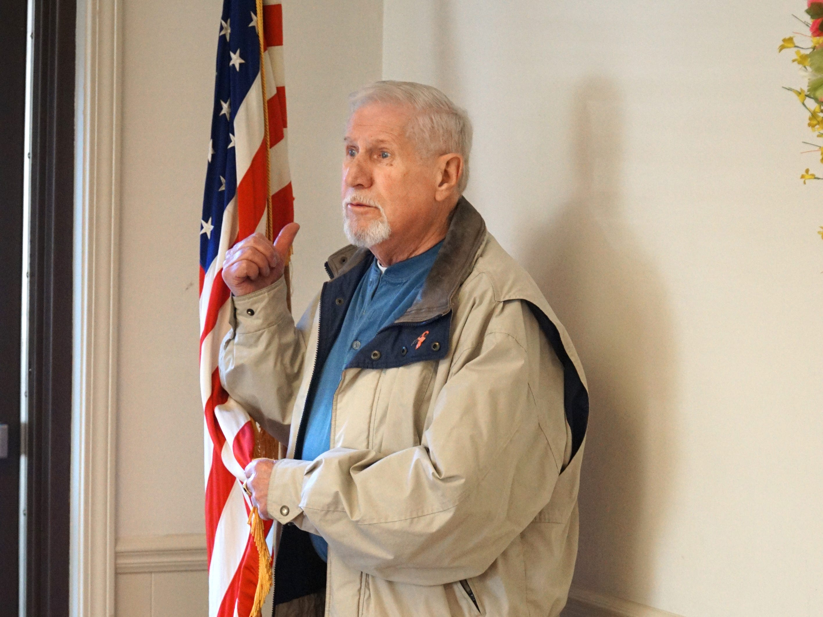 Ivan Emilie holds the American Flag as he leads the Veterans' Lunch in the Pledge of Allegiance on March 18 at the Milford Senior Center.