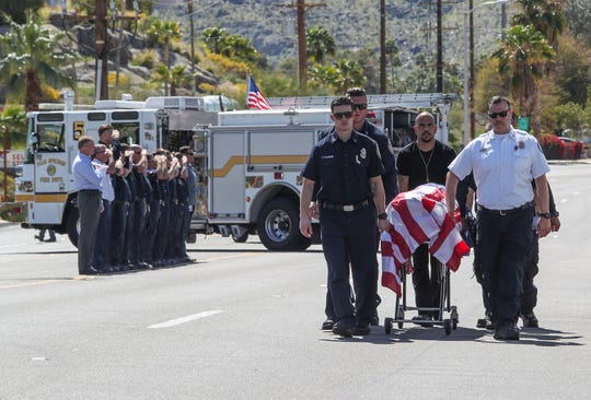 First responders walk the body of an emergency medical technician who was killed while riding his motorcycle to the coroner's van in Palm Springs, March 18, 2019.