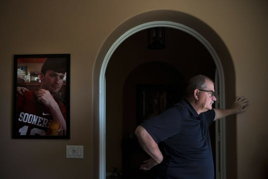 Doug Biggers, whose son, Landon, died of opioid overdose in 2017, pauses in his home office next to a framed photo of his son wearing his favorite jersey, in La Quinta, Calif., on Tuesday, Aug. 14, 2018. For months, Doug sat silently. He pretended when he could that it wasn't real. He nailed two coat hooks to the wall in his home office and hung Landon's jackets there, as though his son had just stopped by.