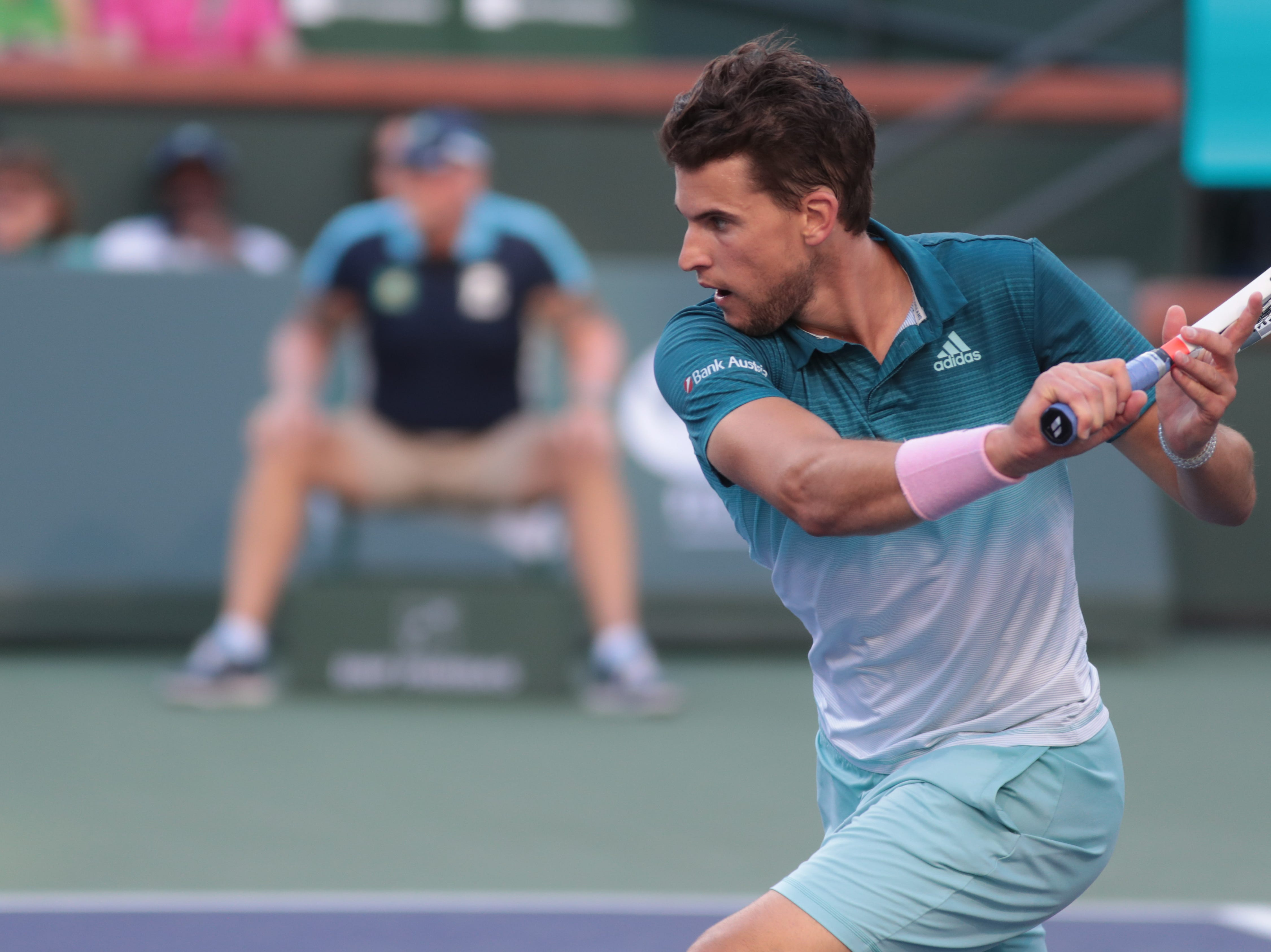 Dominic Thiem moves into the net to hit a backhand to Roger Federer in the finals of the BNP Paribas Open in Indian Wells, Calif., March 17, 2019.