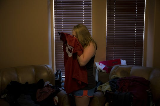 "Brittaney Biggers, whose 20-year-old brother, Landon, died of opioid overdose in 2017, smells a football jersey her brother used to wear in La Quinta, Calif., on Tuesday, Aug. 14, 2018. ""It still smells like him,"" she says. She had moved in with her parents to save money for her own apartment and planned to stay a couple months. Then her brother died, and she picked up a second job at a bar so she could work six days a week and be so tired on the seventh she wouldn't have to face it."