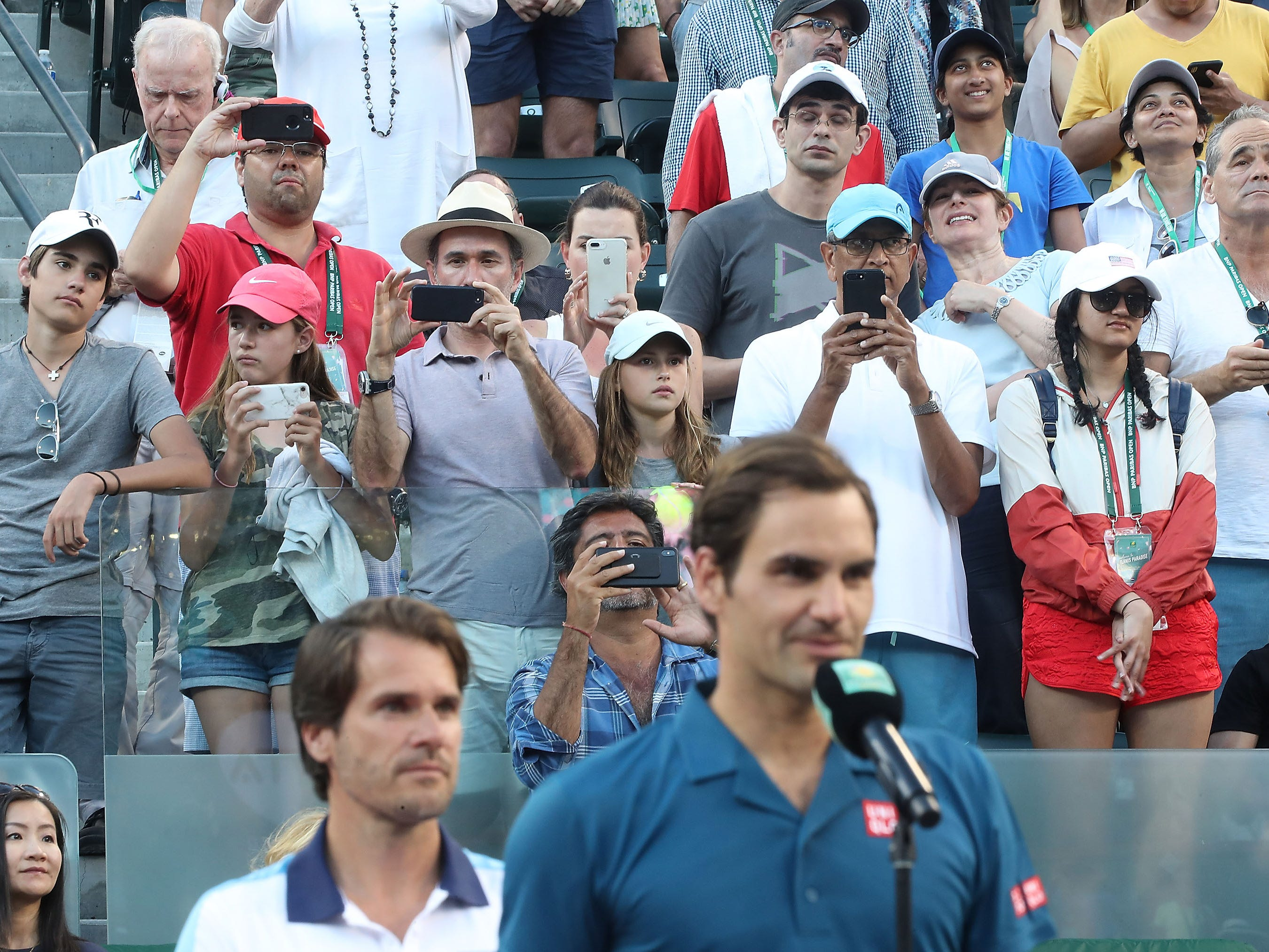 Fans take photos of Roger Federer at the Paribas Open final in Indian Wells, March 17, 2019.
