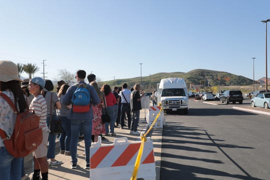 Crowds line the sidewalk at Outlets at Lake Elsinore to board a shuttle for Walker Canyon poppy fields in Lake Elsinore, Calif. on Saturday, March 16, 2019.