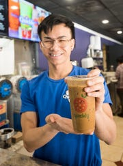 Diep Pham shows off one of Quickly's signature coffee drink available at the restaurant on Monday, March 18, 2019.
