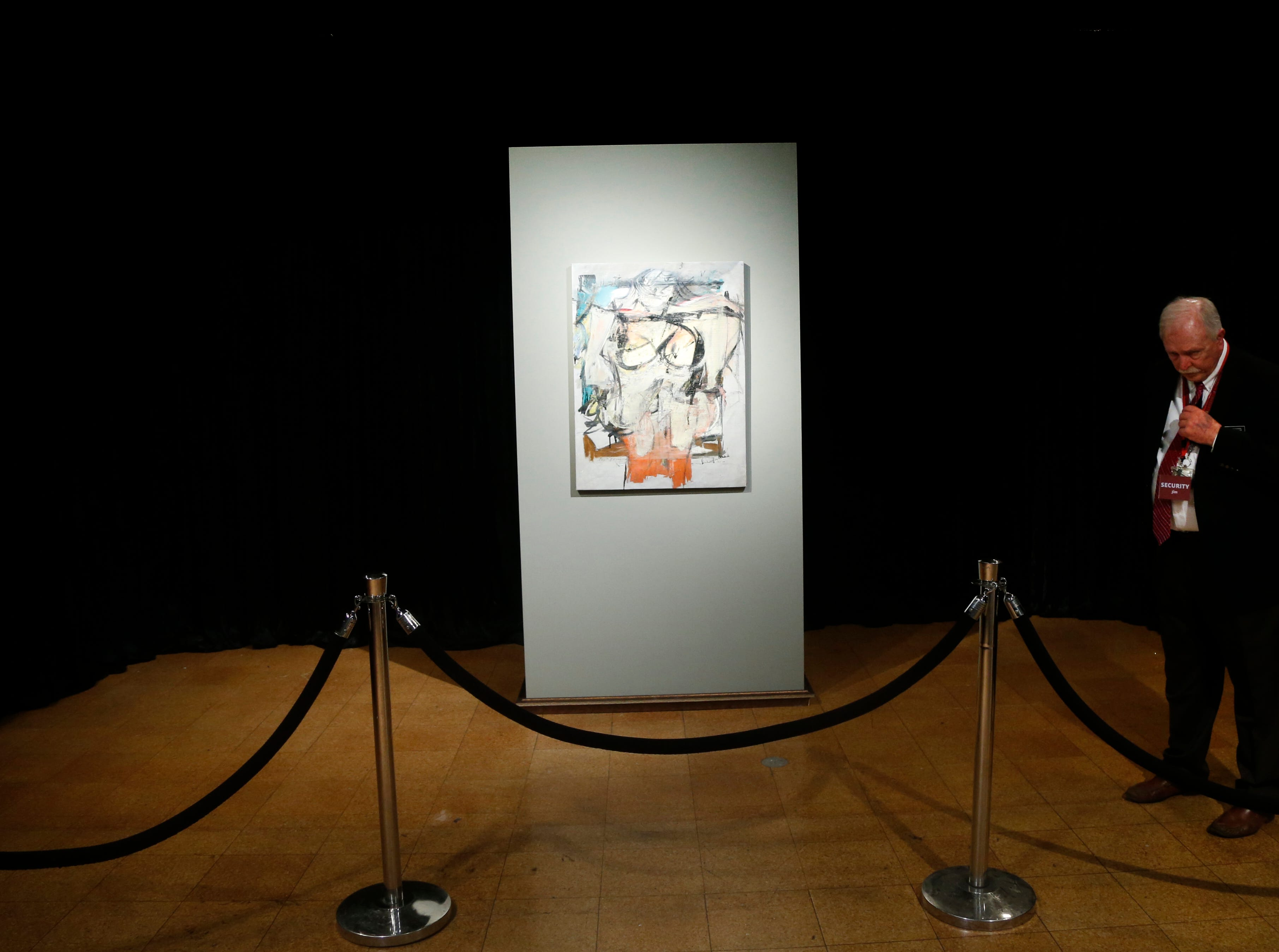 """Waiting for the exhibit to open, security guard Louis Estrella watches over Willem de Kooning's """"Woman-Ochre."""" Stolen in 1985, the painting, recovered in 2017, draws a crowd at the University of Arizona Museum of Art in Tucson on March 17, 2019."""