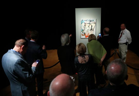 "Sitting on display, Willem de Kooning's ""Woman-Ochre,"" stolen in 1985, draws a crowd at the University of Arizona Museum of Art in Tucson on March 17, 2019."