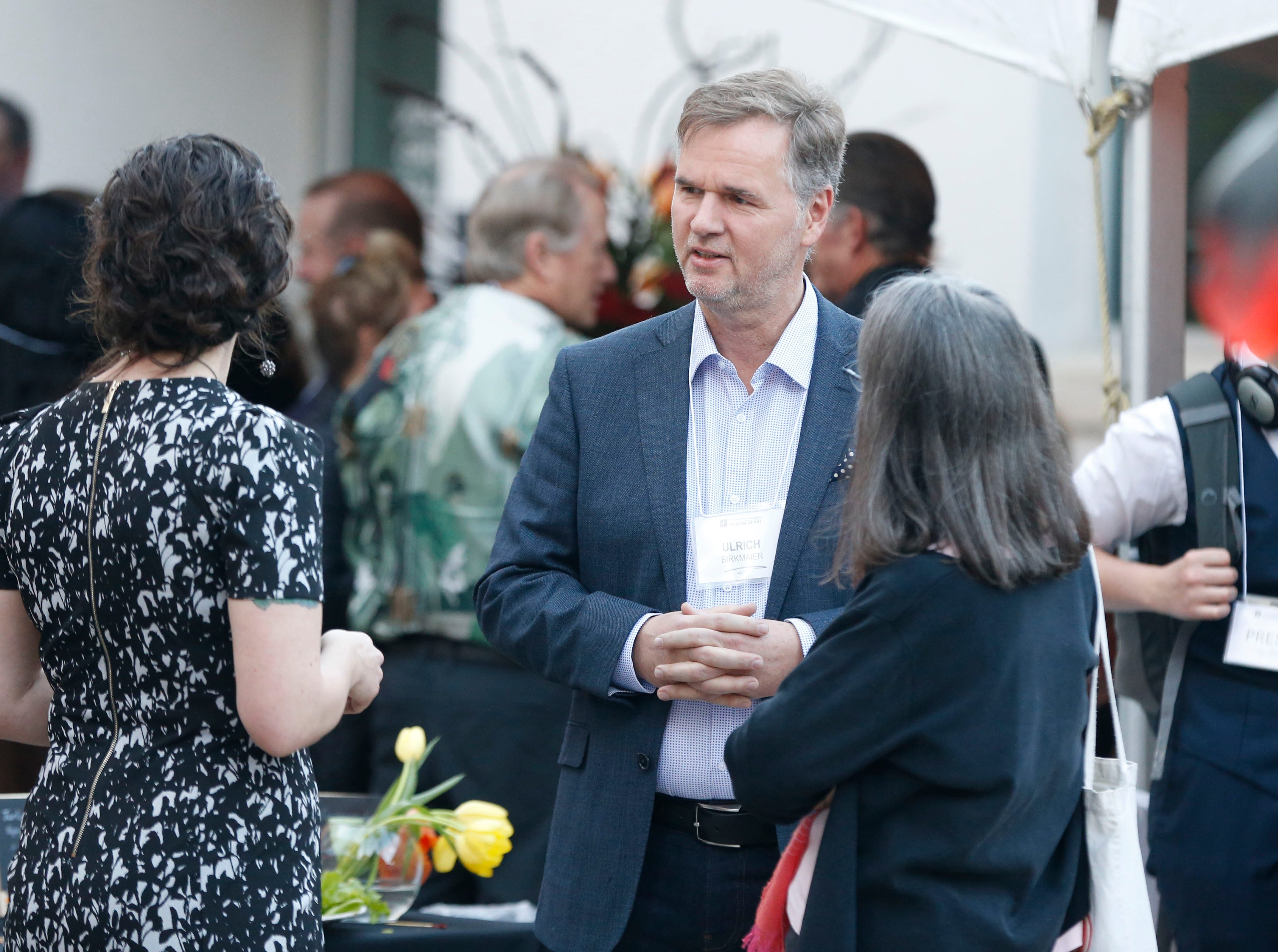 """Getty Museum's Ulrich Birkmaier talks with people at the University of Arizona Museum of Art in Tucson on March 17, 2019. Birkmaier will work on restoring the Willem de Kooning's """"Woman-Ochre,"""" a painting stolen in 1985 from the college."""
