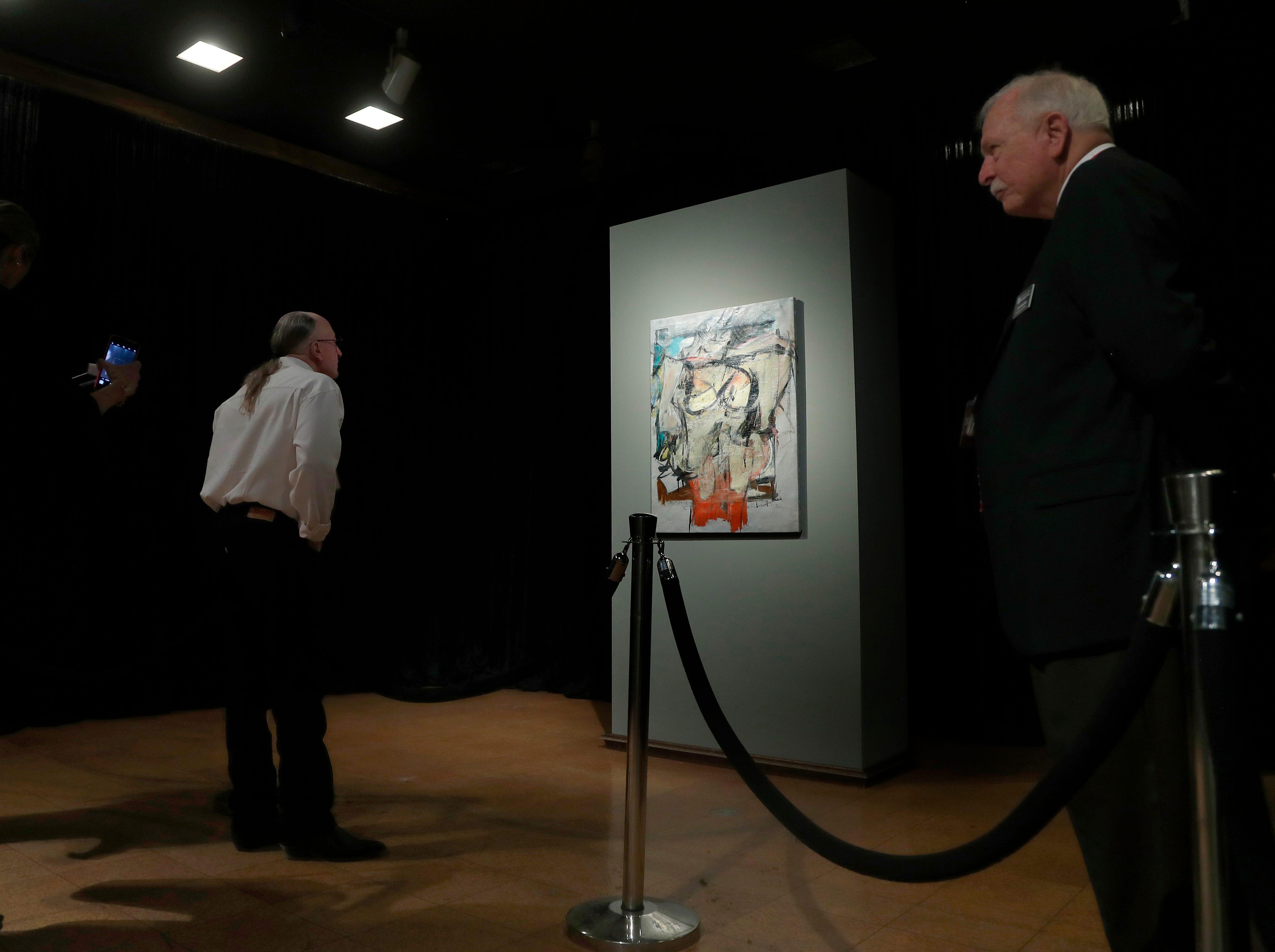"""Sitting on display, Willem de Kooning's """"Woman-Ochre,"""" stolen in 1985, draws a crowd at the University of Arizona Museum of Art in Tucson on March 17, 2019."""
