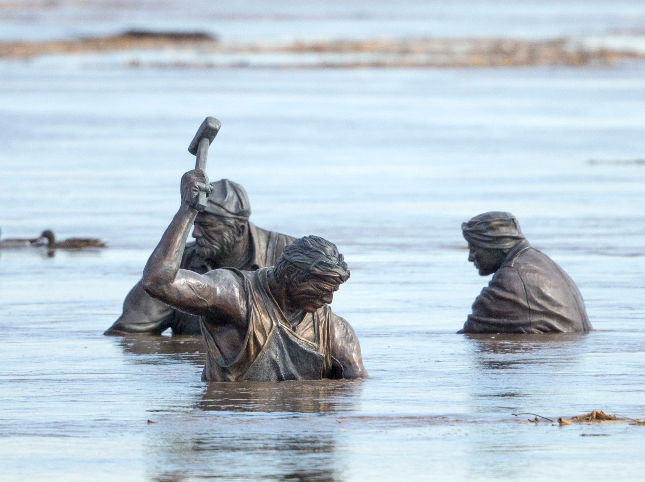 Ducks swim nearby as the high waters of the Missouri River almost submerge figures in the Monument to Labor statue by Matthew J. Placzek, in Omaha, Neb., Saturday, March 16, 2019. Thousands of people have been urged to evacuate along eastern Nebraska rivers as a massive late-winter storm has pushed streams and rivers out of their banks throughout the Midwest. (AP Photo/Nati Harnik)