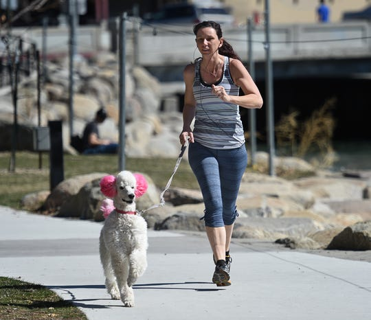 Casandra Woodward jogs by the Truckee River on a spring-like with her dog Vanilla Ice Cream on Monday March 18, 2019. The brief spell of springlike weather is giving way to another round of cold, wet storms Tuesday through Thursday.