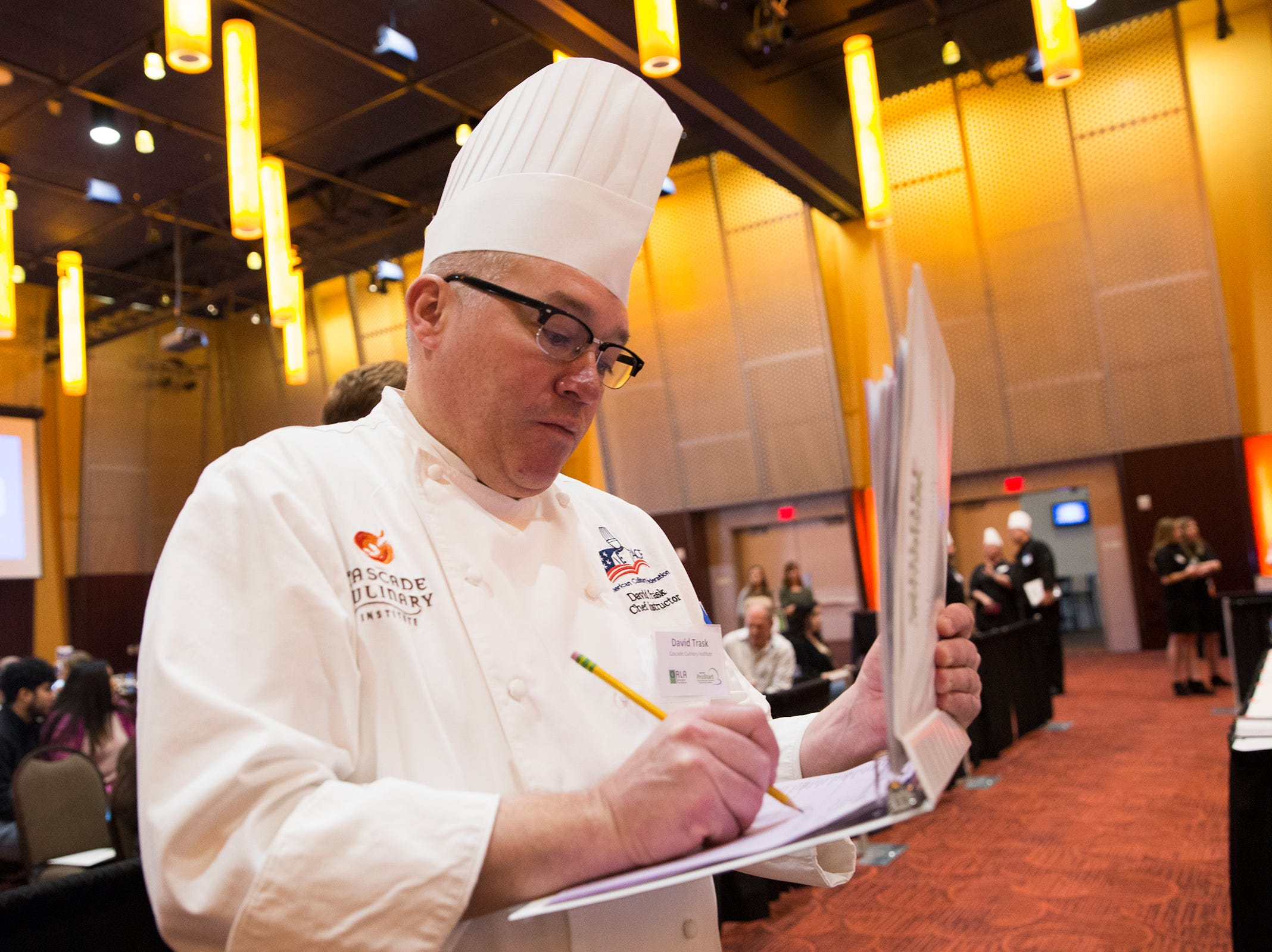 Chef David Trask takes notes during the ORLAEF's ProStart Invitational, a statewide high school culinary competition, at the Salem Convention Center on March 18, 2019.