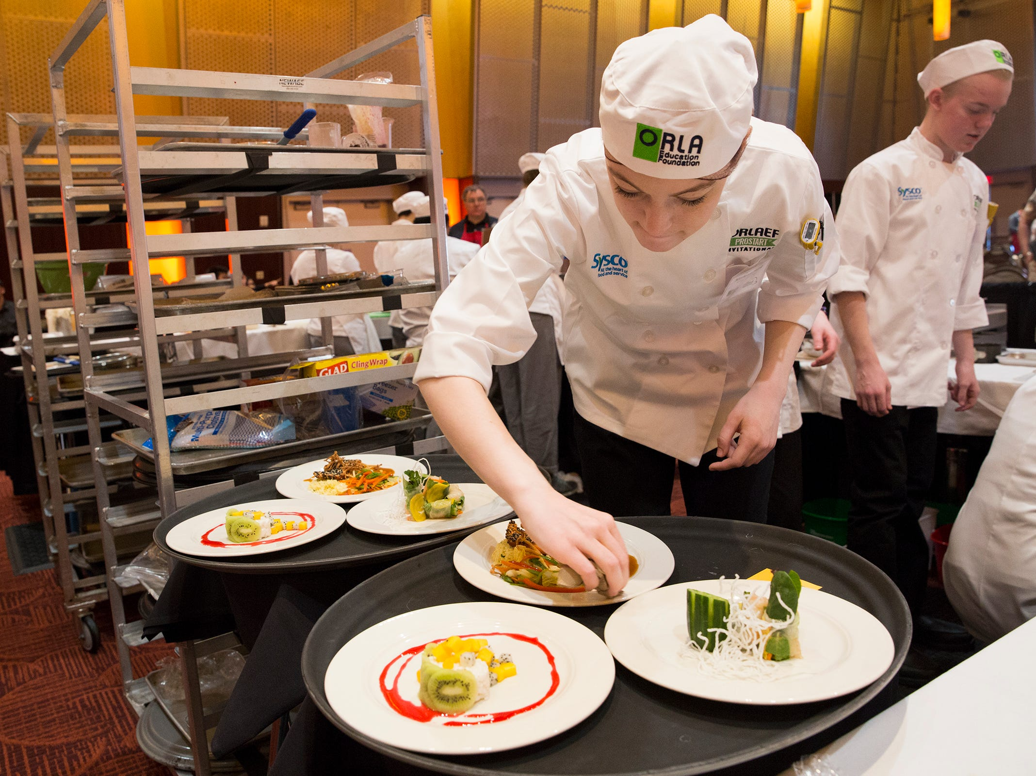 McNary's Madelyn Hurst places the final touches on the teams dishes during the ORLAEF's ProStart Invitational, a statewide high school culinary competition, at the Salem Convention Center on March 18, 2019.