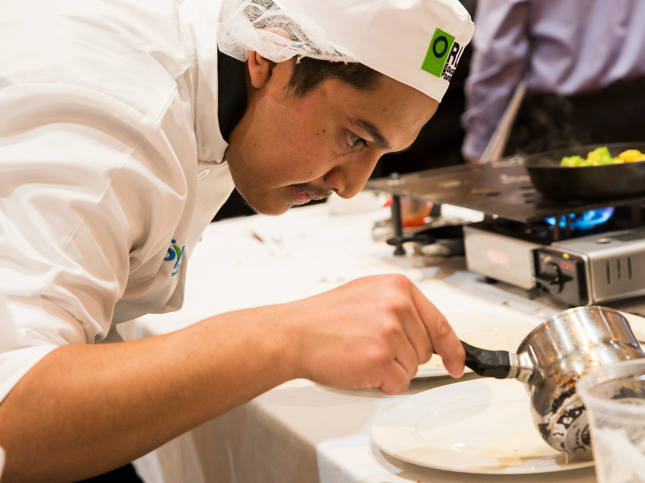 McMinnville's Bryan Lara-Barragan drizzles their supreme sauce onto the main entree dish during the ORLAEF's ProStart Invitational, a statewide high school culinary competition, at the Salem Convention Center on March 18, 2019.