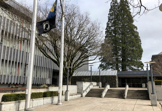 Flags, including a POW/MIA flag, flap in a breeze in front of the Lane County Circuit Court building where the Veterans Treatment Court is held in Eugene.