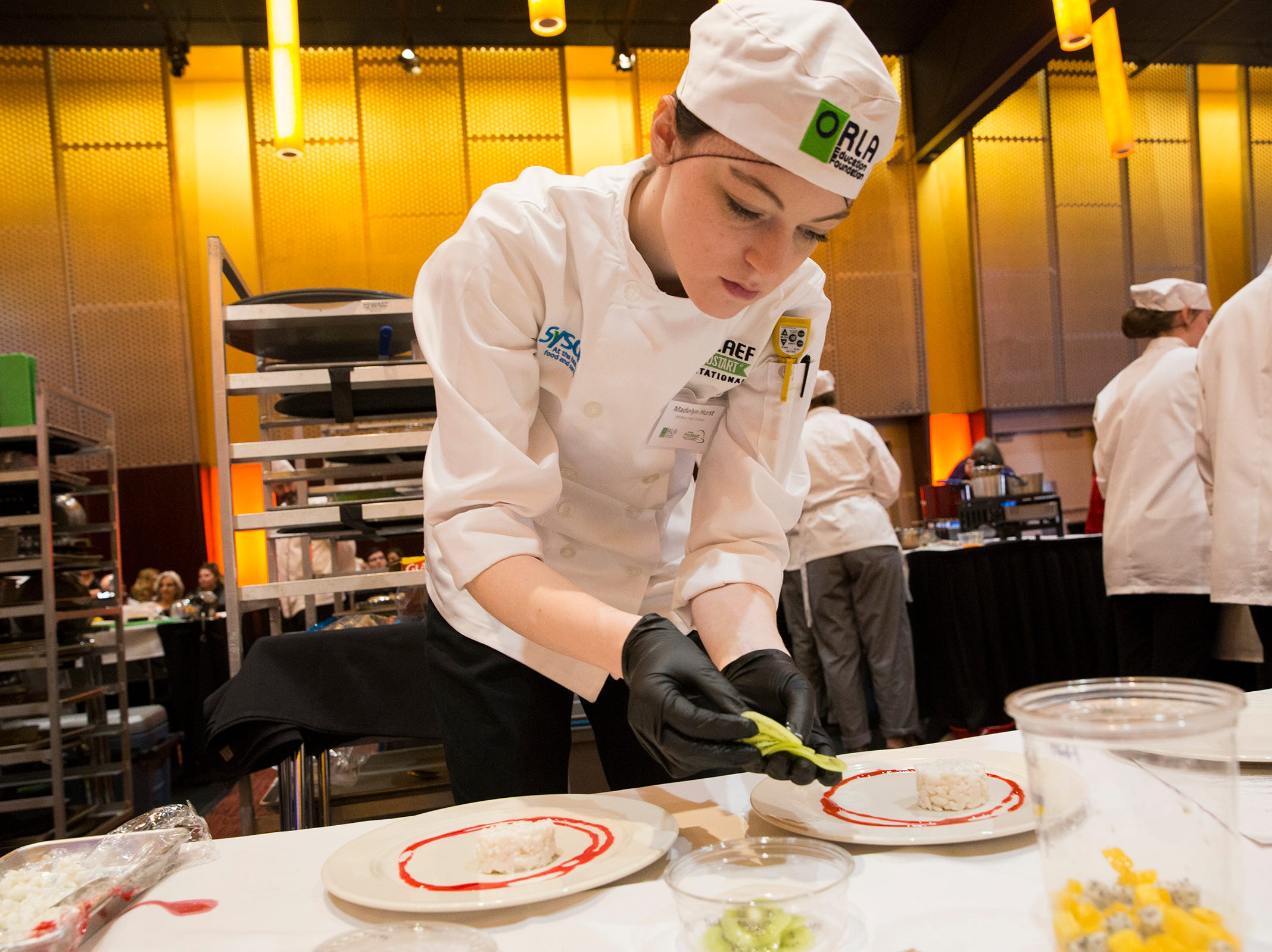 McNary's Madelyn Hurst places slices of kiwi around a rice dish during the ORLAEF's ProStart Invitational, a statewide high school culinary competition, at the Salem Convention Center on March 18, 2019.