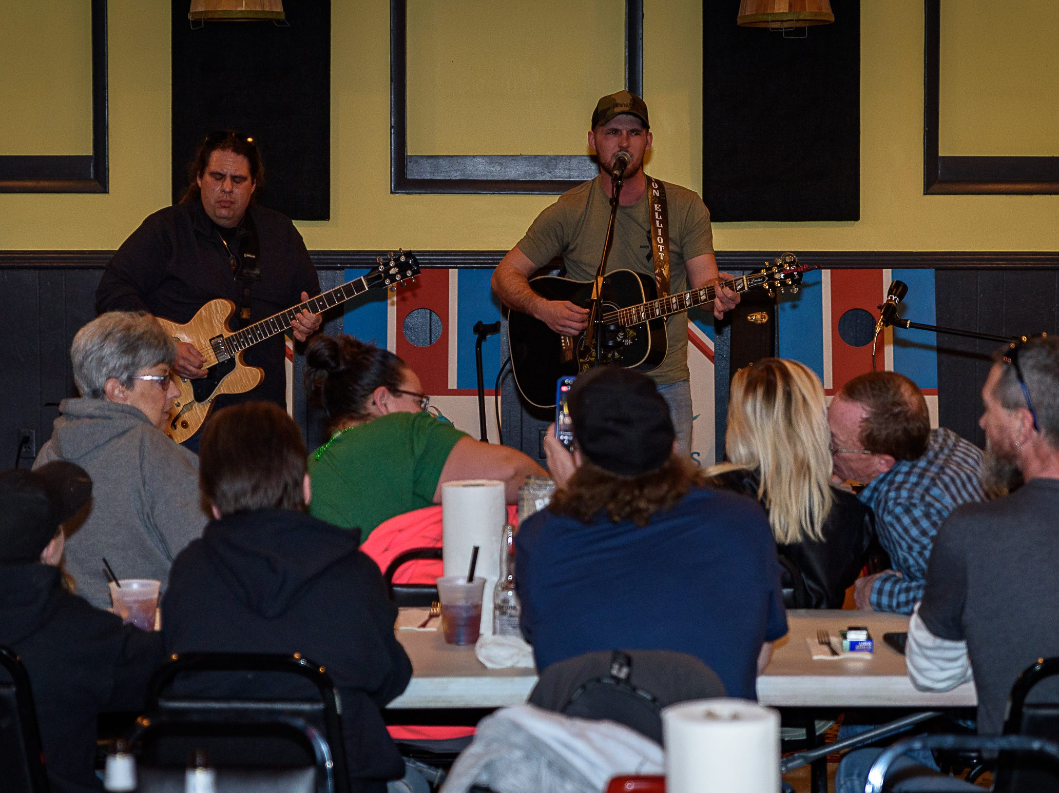 "Singer Dalton Elliott (right) performs during a watch party at Steamers Restaurant and Sports Bar on Chincoteague Island before his ""American Idol"" debut on Sunday, March 17, 2019. Elliott lives on Chincoteague."