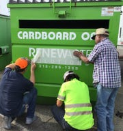 Bossier Parish Police Jury and Renewaste workers put the finishing touches on one of three new recycle bins.