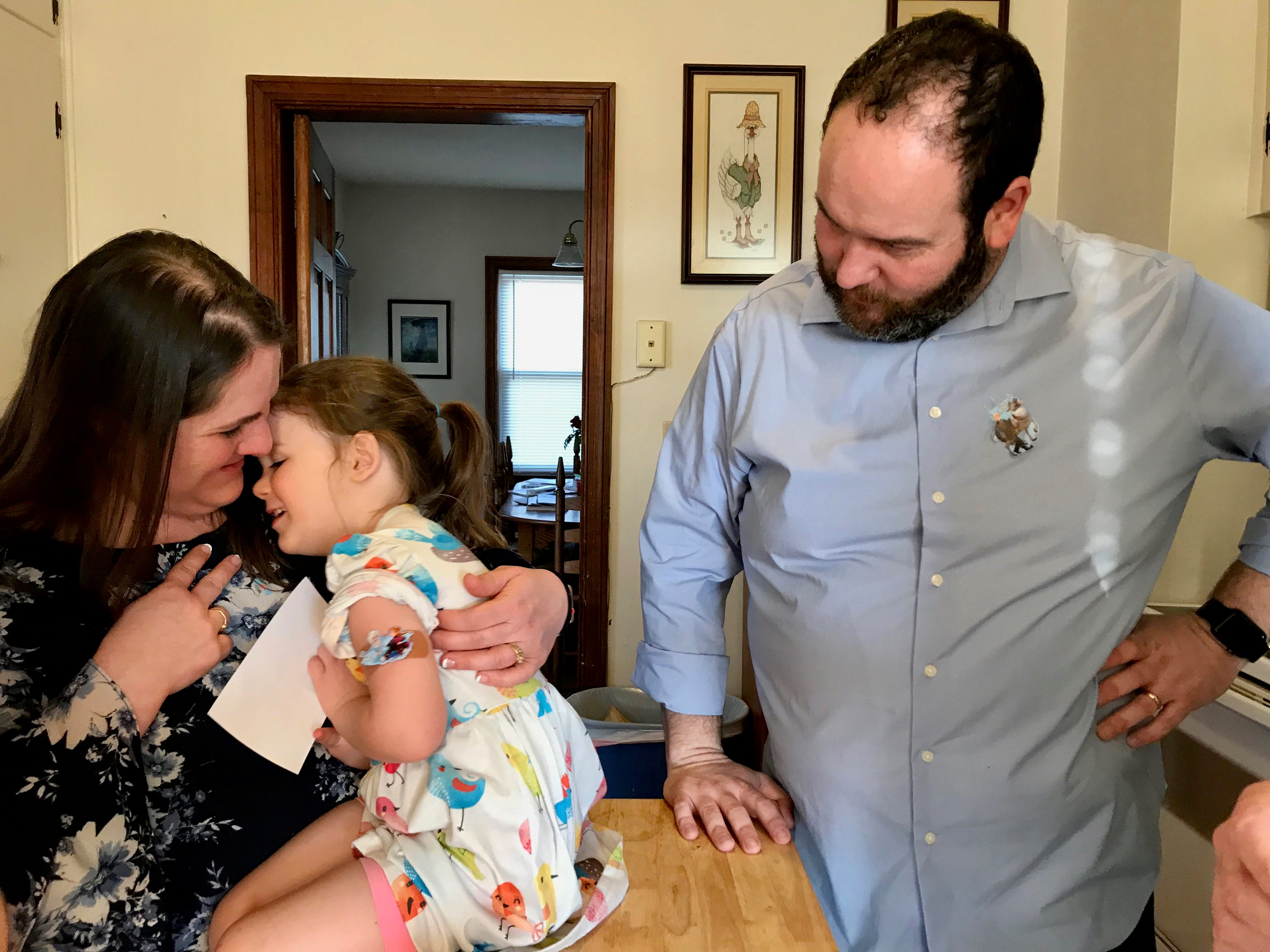 Mom and dad Amy and Brent Bussey with their daughter Rebecca, 3, after she received her monthly injection on Friday, March 15, 2019 in their home in Ladd, Virginia. Rebecca has the rare disease Systemic Juvenile Idiopathic Arthritis and gets a monthly dose of the biologic medication Ilaris.