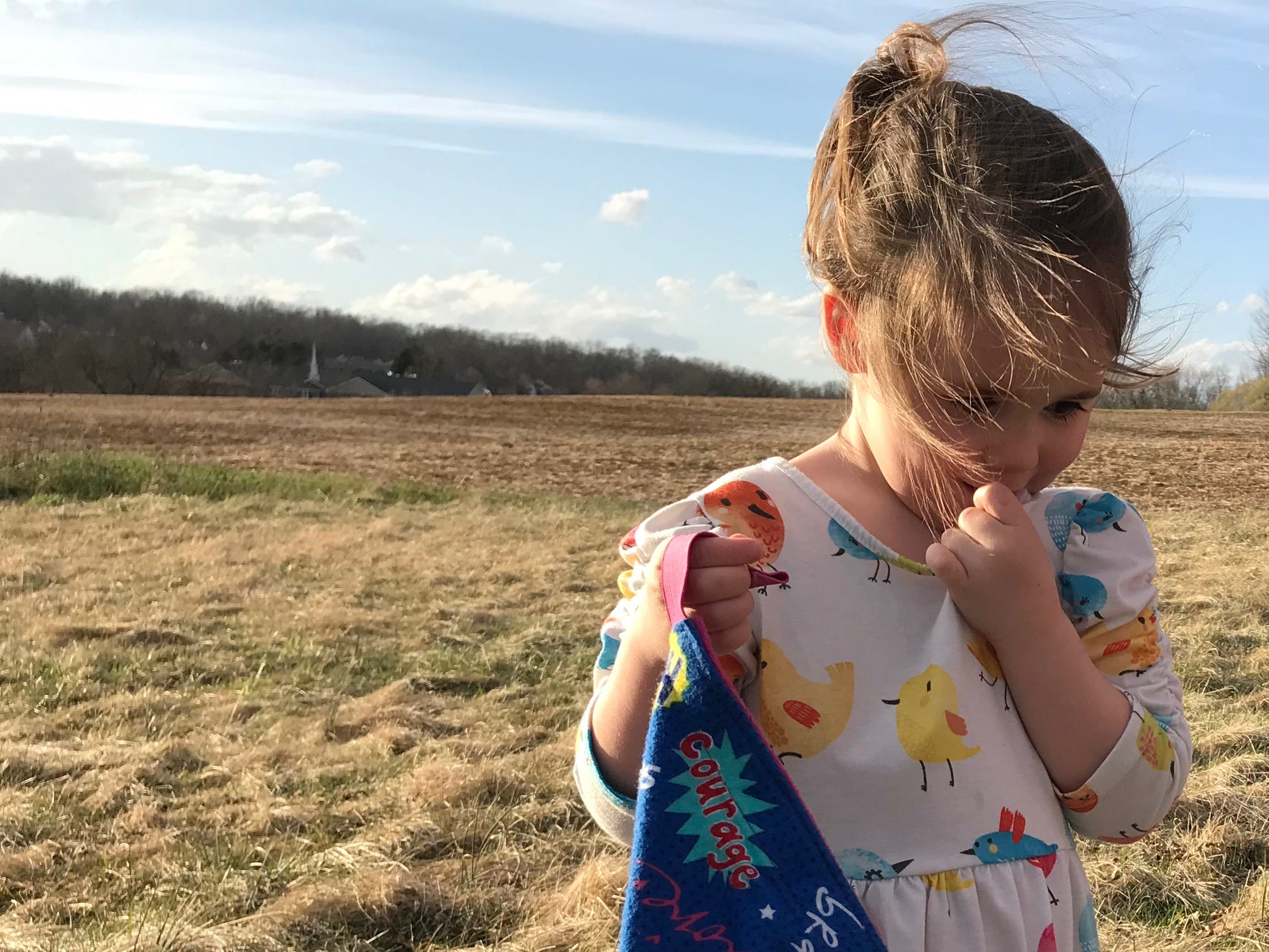Rebecca Bussey, 3, holds her superhero cape while playing in her backyard in Ladd, Virginia, on Friday, March 15, 2019. An organization called Tiny Superheroes makes capes for kids with chronic diseases. Bussey has Systemic Juvenile Idiopathic Arthritis.