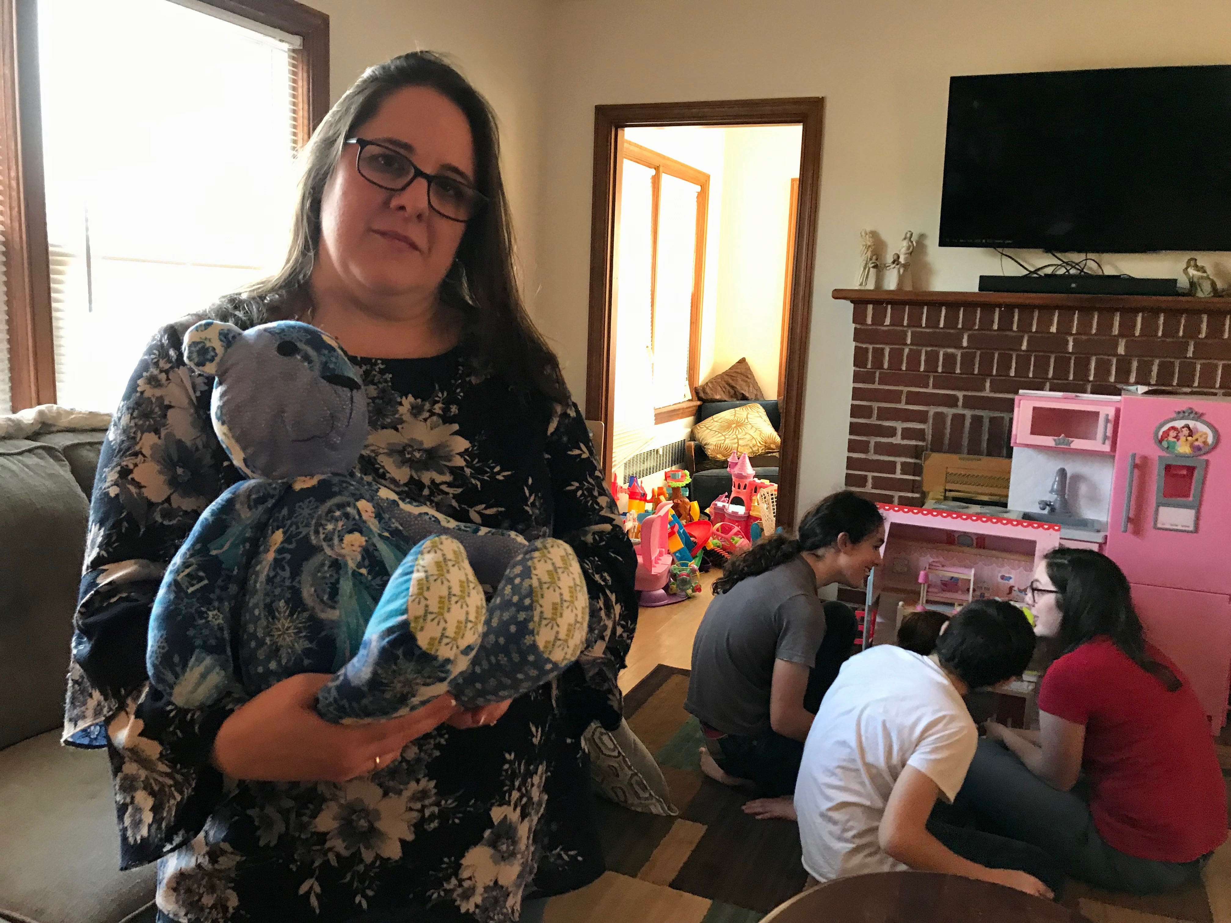 Amy Bussey holds her daughter Rebecca's Rare Bear while her kids Carter, Wyatt and Julia gather round Rebecca as she plays with her dollhouse in their home in Ladd, Virginia, on Friday, March 15, 2019.