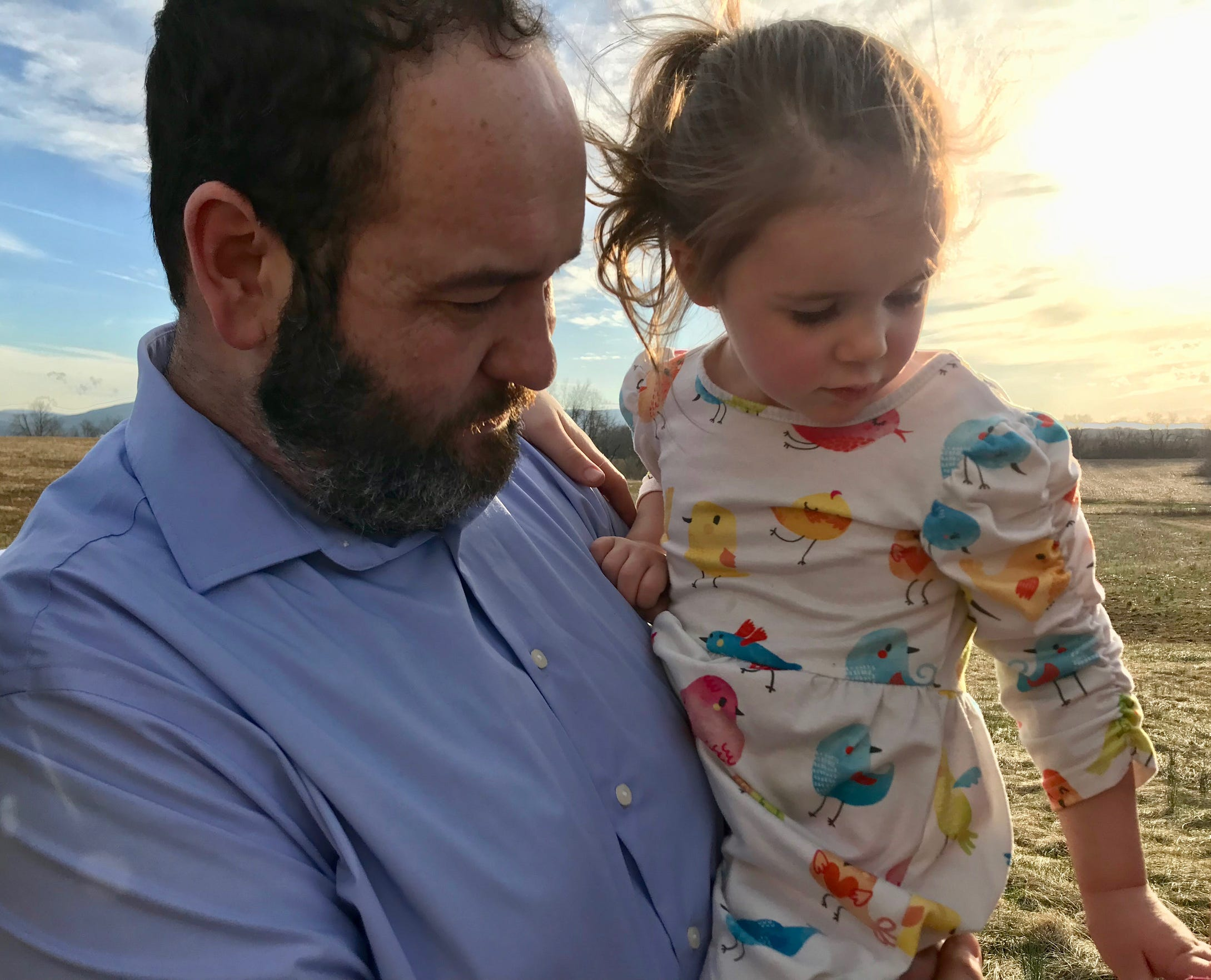 """""""I feel like I'm waiting for the other shoe to drop. I'm constantly in a state of alert waiting for something to happen."""" Brent Bussey holds his daughter Rebecca, 3, in the backyard of their home in Ladd, Virginia, on Friday, March 15, 2019. Rebecca has the rare disease Systemic Juvenile Idiopathic Arthritis."""