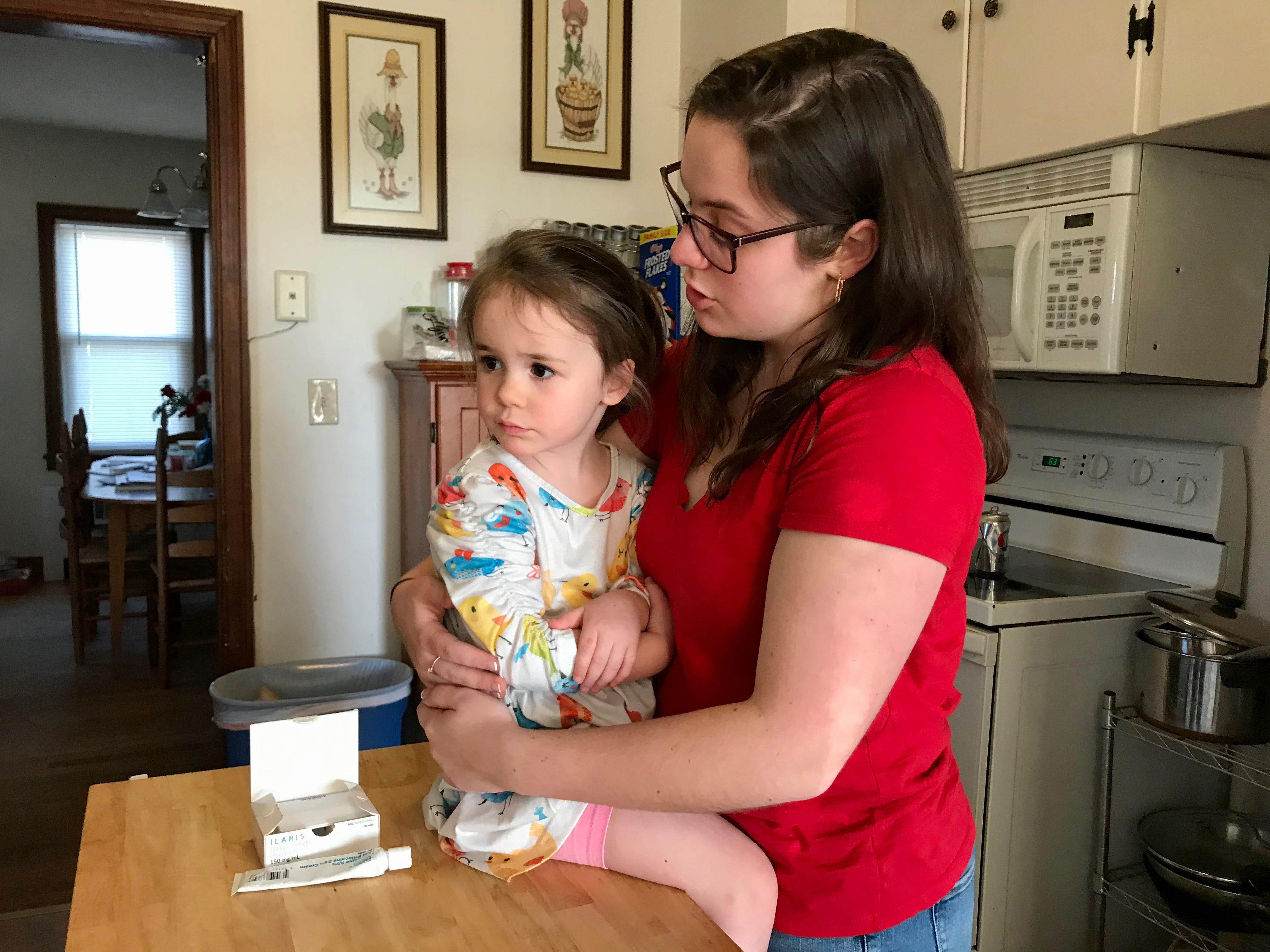 Big sister Julia Bussey, 19, holds her sister Rebecca Bussey, 3, while Rebecca's nurse is preparing a syringe for injection. Rebecca gets a monthly dose of the biologic medication Ilaris made by Novartis to treat Systemic Juvenile Idiopathic Arthritis. Photograph taken on Friday, March 15, 2019 in Ladd, Virginia.