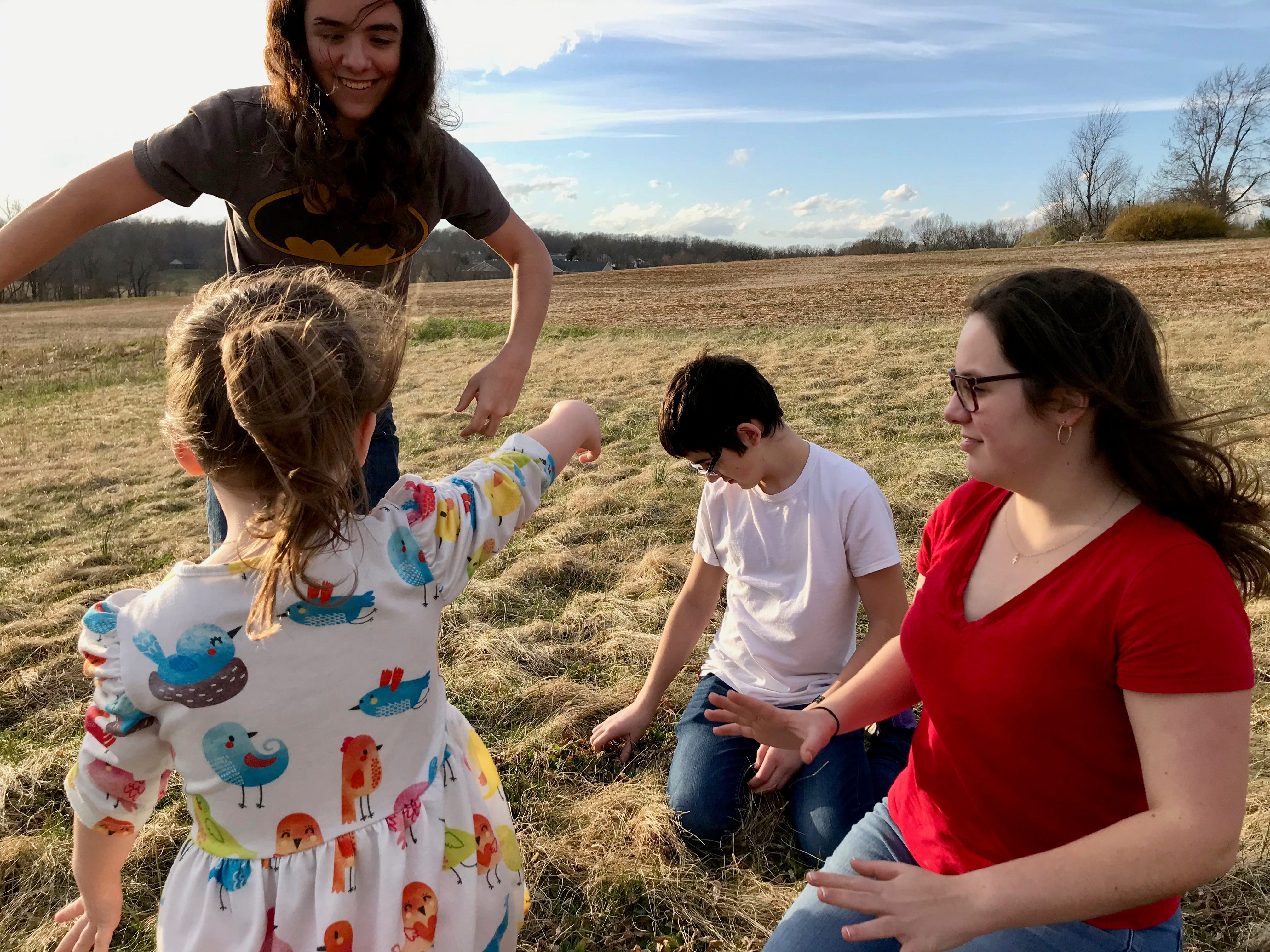 Carter Bussey, 15, Wyatt Bussey, 14, and Julia Bussey, 19, play with their sister Rebecca Bussey, 3, in the backyard of their home in Ladd, Virginia, on Friday, March 15, 2019. Rebecca Bussey has the rare disease Systemic Juvenile Idiopathic Arthritis.