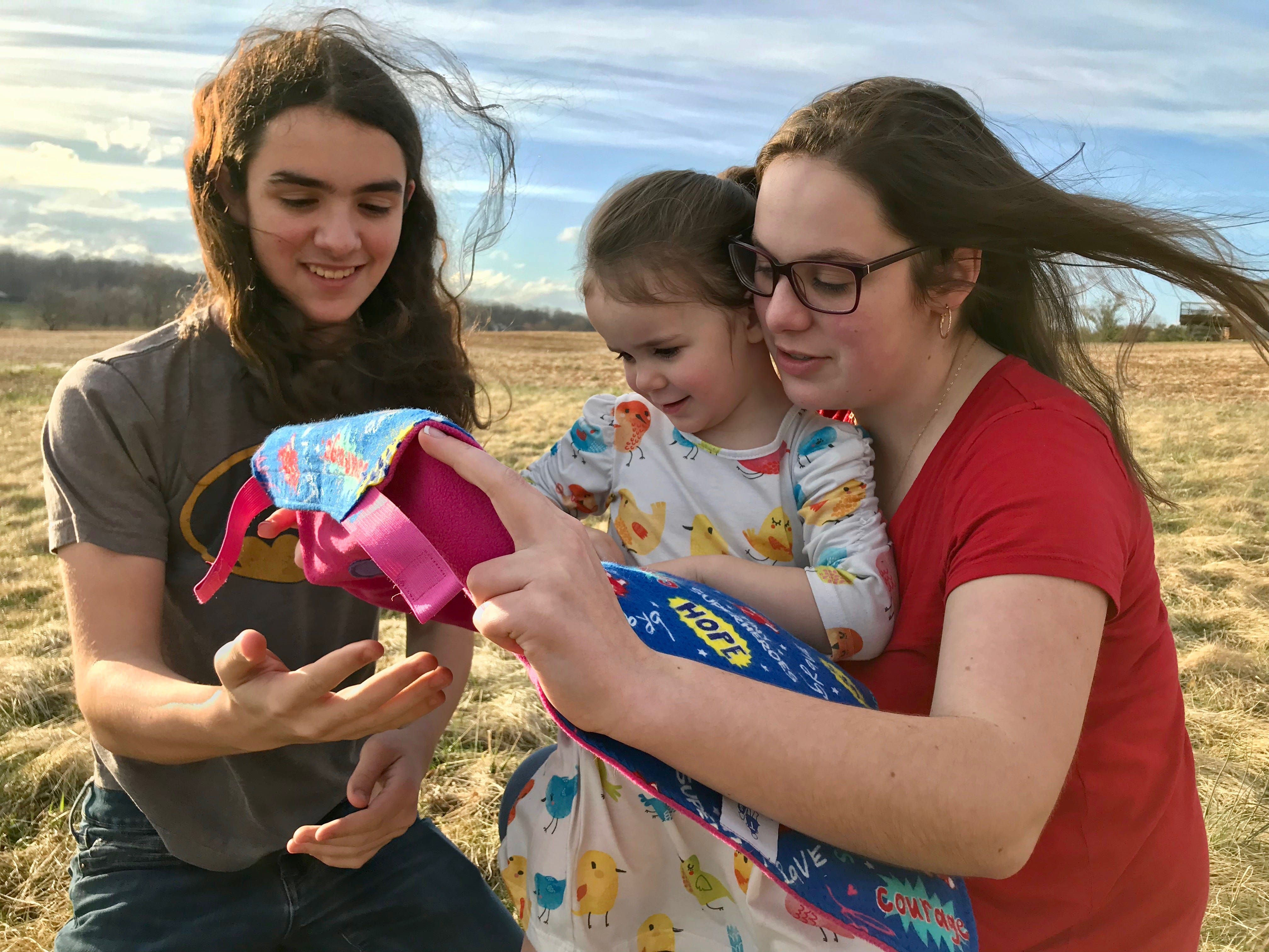 Carter Bussey, 15, and Julia Bussey, 19, hold their sister Rebecca Bussey, 3, while they look at her Tiny Superheroes cape in the backyard of their home in Ladd, Virginia, on Friday, March 15, 2019. Rebecca Bussey has the rare disease Systemic Juvenile Idiopathic Arthritis.