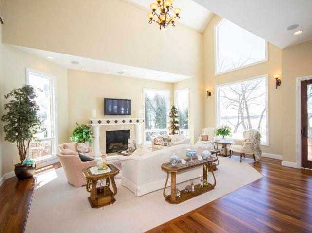 The living room has large windows and a classy fireplace.