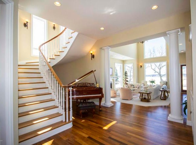 Once inside, the home shines with marble floors, a spiral staircase and a look in at the living room's hardwood floors and classy fireplace.