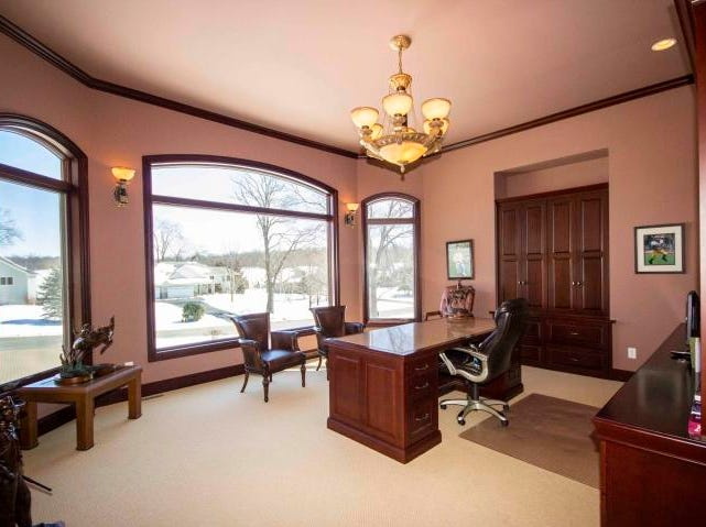 A spacious executive office with rich built-in cabinetry and crown moldings occupies one of the home's castle-like turrets.