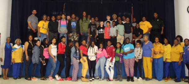 """""""Mission Possible"""" Youth Symposium participants sponsored by the Tallahassee Alumnae Chapter of Sigma Gamma Rho Sorority, Inc., with Griffin Middle School administration, school resource officer, and local author."""