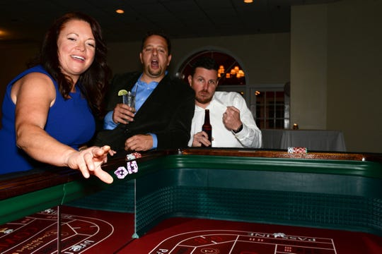 "Molly Gereaud, left, rolls the dice as  Anthony Swann and Mike Shelly cheer her on at Renaissance Charter School of St. Lucie's ""Viva Las Vegas"" gala and benefit auction."