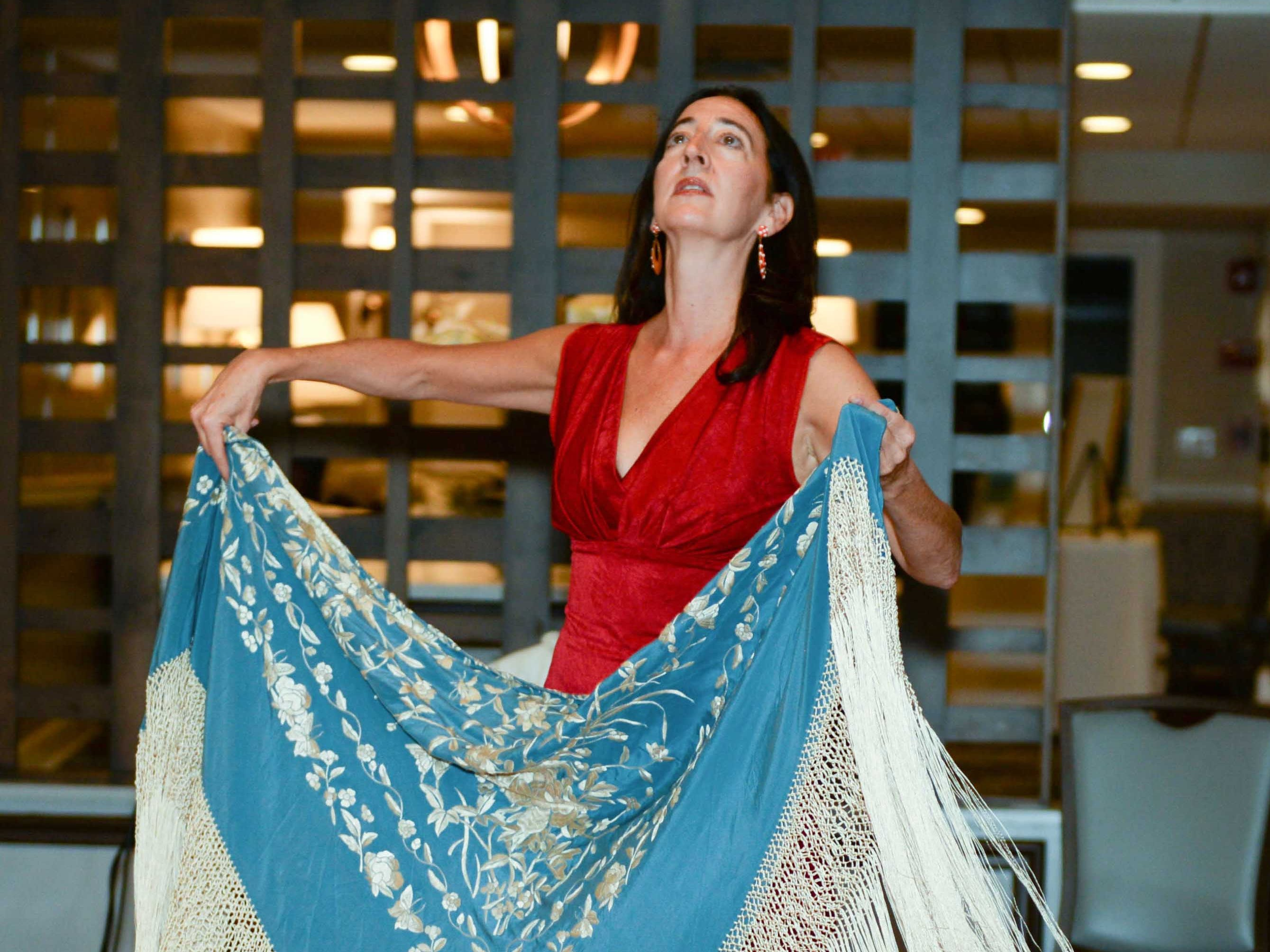 Flamenco dancer Eva Conti shows the audience a handmade dance shawl during the Meet the Artist Dinner at the Stuart Yacht & Country Club.
